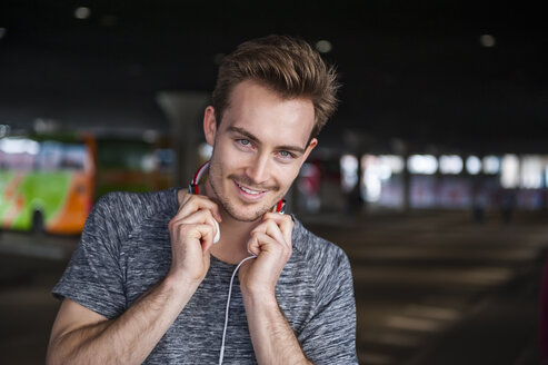 Portrait of smiling young man with headphones - DIGF000333