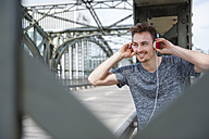 Portrait of smiling young man on a bridge listening with headphones - DIGF000336