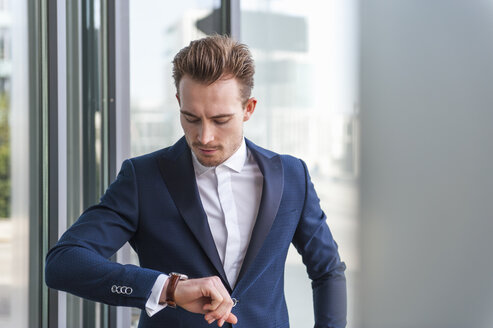 Portrait of young man wearing suit checking the time - DIGF000339