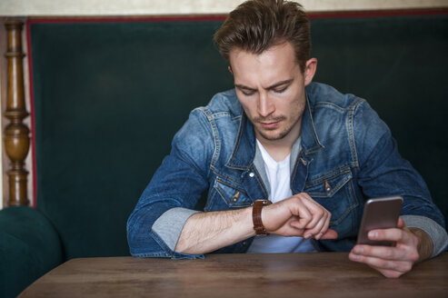 Portrait of angry young man sitting in a coffee shop checking the time - DIGF000345