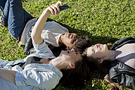 Three girl friends lying on grass taking selfie with smart phone - MAUF000445