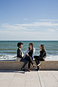 Three young woman sitting by the sea, talking - MAUF000448