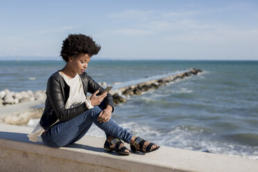 Young woman sitting by the sea, using smart phone - MAUF000451
