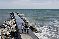Three young women walking on breakwater at the sea, rear view - MAUF000454