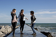 Three young women having fun on breakwater at the sea - MAUF000457