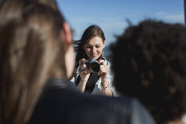 Young woman with camera photographing friends - MAUF000460