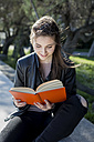 Young woman in park reading book - MAUF000463