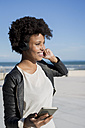 Young woman listening music with smart phone - MAUF000466