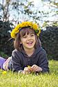 Portrait of smiling little girl lying on meadow wearing floral wreath of dandelions - LVF004781