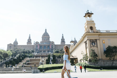 Spain, Barcelona, Young woman on sightseeing tour in front of museum - JRFF000554
