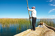Peru, Titicaca lake, Uros Floating Villages, man wearing chullo hat on a traditional reed boat - GEM000874