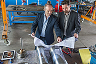 Two engineers with construction plan in front of hydraulic cylinder - DIGF000356