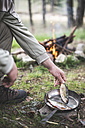 Man's hand putting rudd into a pan for frying at camp fire - DEGF000781