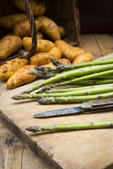 Green asparagus and pocket knife on wooden board - LVF004796