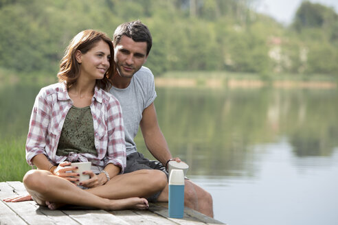 Portrait of relaxed young couple with coffee mugs sitting on a jetty at lake - ZOCF000053