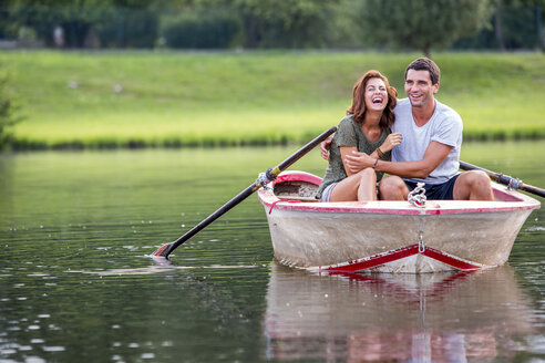 Young couple having fun in a rowing boat on lake - ZOCF000062
