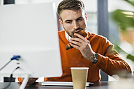 Young man having a snack at desk in office - UUF007103