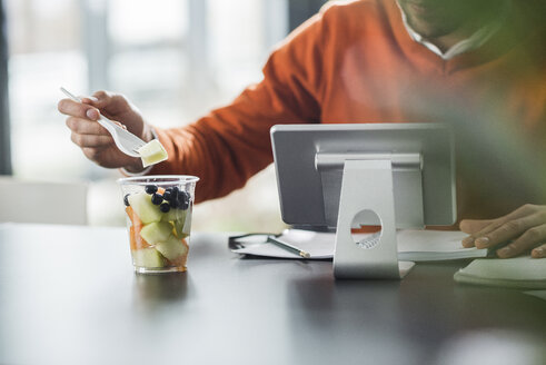 Young man having a fruit salad at desk in office - UUF007106