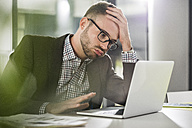 Discontent young man with laptop in office - UUF007109