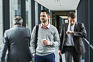 Calm businessman in contrast to businessmen in a hustle - UUF007163