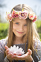Portrait of smiling girl with wreath of flowers holding magnolia blossom in her hands - SARF002701