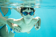 Young boy diving, mother is helping, sticking out tongue, under water, swimming pool - ZOCF000068