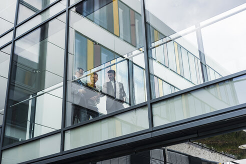 Three businessmen behind glass facade, passage - UUF007170