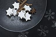 Cinnamon stars, cinnamon sticks, star anise and decoration on metal plate - ASF005887