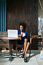 Young woman with laptop sitting in a street cafe drinking coffee - KIJF000331