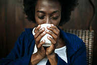 Woman's hands holding cup of coffee, close-up - KIJF000337