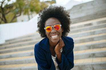 Portrait of happy young woman with nose piercing wearing mirrored sunglasses - KIJF000349