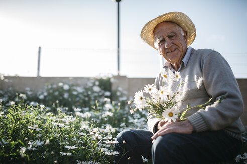 Portrait of senior man with picked flowers in his garden - JRFF000581