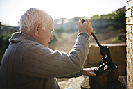 Senior man using an old tool for cracking walnuts - JRFF000596
