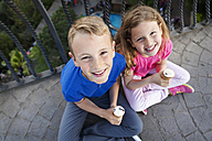 Portrait of brother and sister with ice cream cones sitting on balcony looking up to camera - VABF000472
