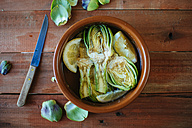 Clay pot with sliced artichokes in water with lemon - KIJF000361