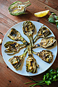Grilled artichokes served on plate - KIJF000370