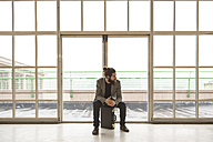 Hipster businessman with briefcase waiting in front of door in industrial building - ZOCF000093