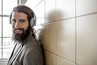 Young bearded man listening music with headphones - ZOCF000099