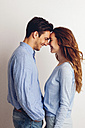 Happy young couple standing face to face in front of white background - CHAF001654
