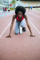 Young black athlete preparing for race in stadium - KIJF000372