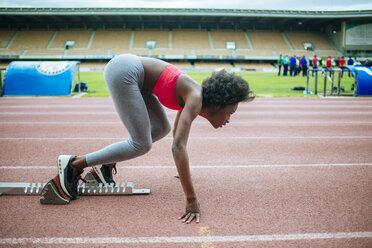 Young black athlete preparing for race in stadium - KIJF000375