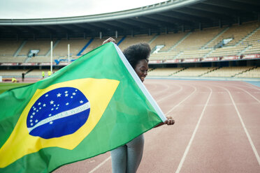 Young black athlete in stadium carrying Brazilian flag - KIJF000378