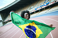 Young black athlete in stadium carrying Brazilian flag - KIJF000381