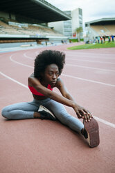 Young black athlete stretching before race in stadium - KIJF000384
