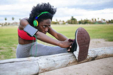 ng black athlete listening music with headphones while warming up - KIJF000390