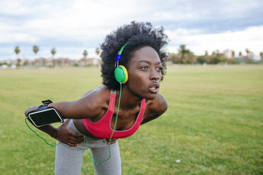 ng black athlete listening music with headphones while warming up - KIJF000393