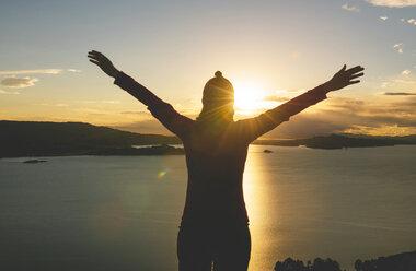 Peru, Amantani Island, silhouette of woman with raised arms enjoying sunset from Pachamama peak - GEMF000878