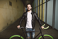 Smiling young man with fixie bike - RAEF001091