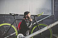Young man carrying fixie bike - RAEF001097