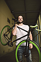 Smiling young man carrying fixie bike - RAEF001118